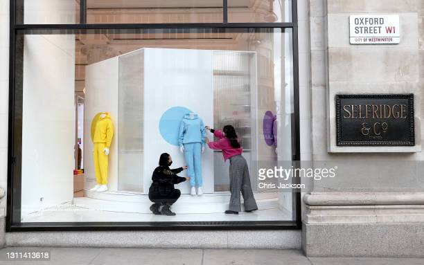 Selfridges employees puts the final touches to the window display at Selfridges on April 08, 2021 in London, England. All non-essential retail will...