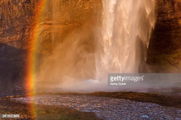 Seljalandsfoss waterfall base and rainbow, sunset