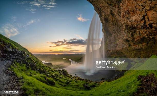 seljalandsfoss waterfall is mind-blowingly spectacular. blue sky, with a peek of sunlight considering this was taken at half past ten at night. the waterfall drops an impressive 60 meters into the plunge pool. surrounded by lush green countryside. - behind waterfall stock pictures, royalty-free photos & images