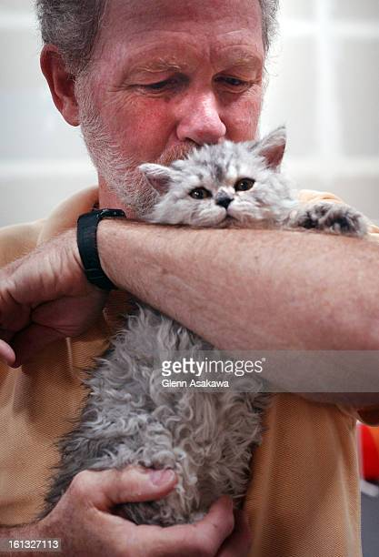 Selkirk <cq> Rex <cq> breed of cat is hugged by its owner Arnold <cq> Farley <cq> after running a cat agility course set up in an old office space in...