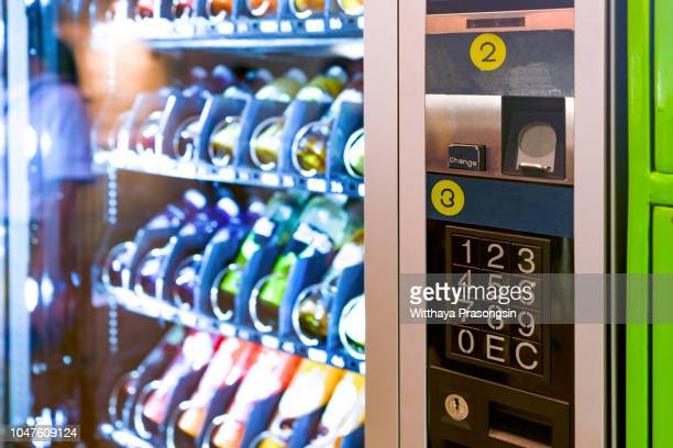 sell, technology and consumption concept - pushing button on vending machine operation panel - vending machine stock photos and pictures