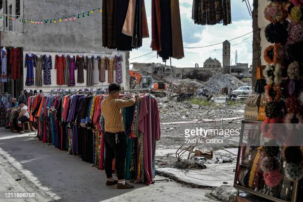 Seller arranges clothes put on display at the Sarj Khaneh market area in the old city of Iraq's northern Mosul, while the damaged Roman Catholic...
