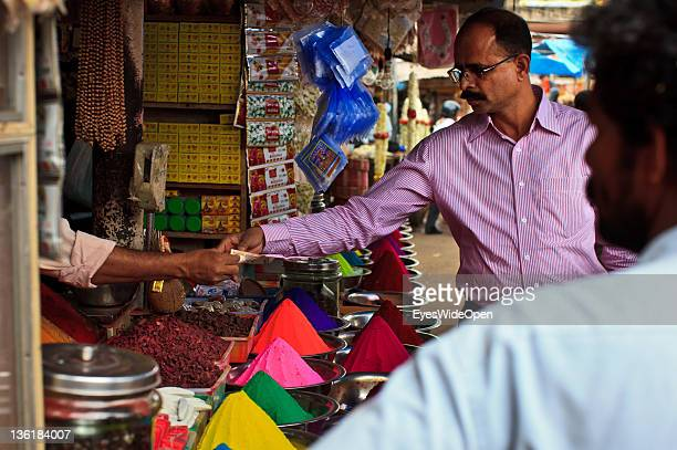 Seller at the famous and colourful Devaraja Market and bazaar offering vegetables, fruits and conicle piles of kumkum at December 18, 2011 in Mysore,...