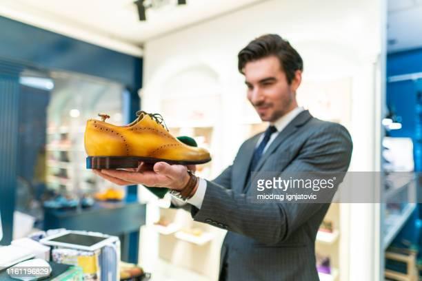 verkoper clerk holding elegante schoenen in de winkel - witte schoen stockfoto's en -beelden