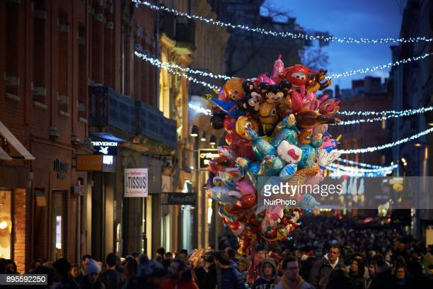 A seller of balloons in the streets of Toulouse A Christmas market is placed on the main square of Toulouse the Capitole People come to buy a hot...