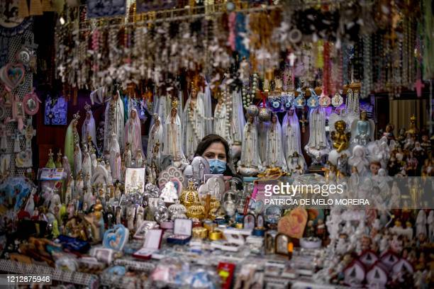 Seller of religious figurines poses at her stall wearing a face mask during the 103rd anniversary of the apparitions of Our Lady of Fatima at the...