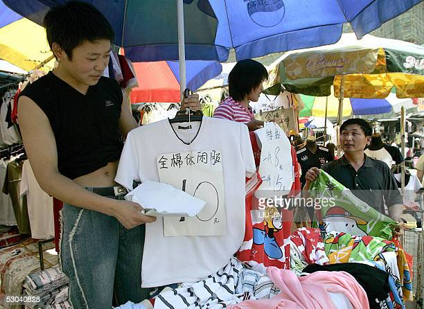 A seller promotes his Tshirt at a stall in a clothing wholesale market in Shanghai 09 June 2005 Chinese Commerce Minister Bo Xilai said developed...