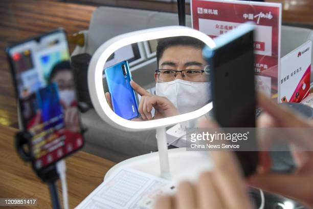 A seller promotes smartphones through live streaming at a counter on March 2 2020 in Taiyuan Shanxi Province of China The salesman said that he can...
