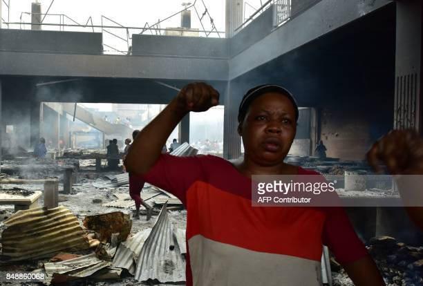 A seller reacts amid debris in the market after a fire devastated the building during the night on September 18 2017 in Abobo neighborhood of Abidjan...