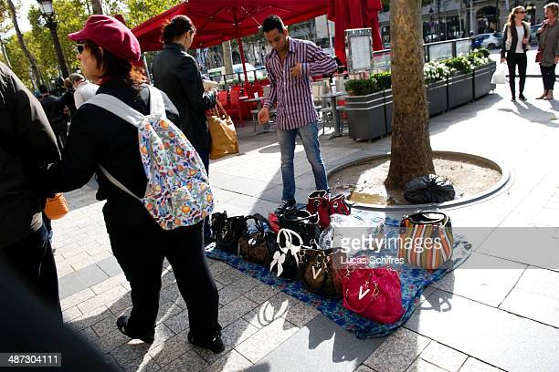 A seller sells fake bags on famous Champs Elysees avenue in Paris on October 17 2013 According to a disputed report from Le Figaro newspaper London...