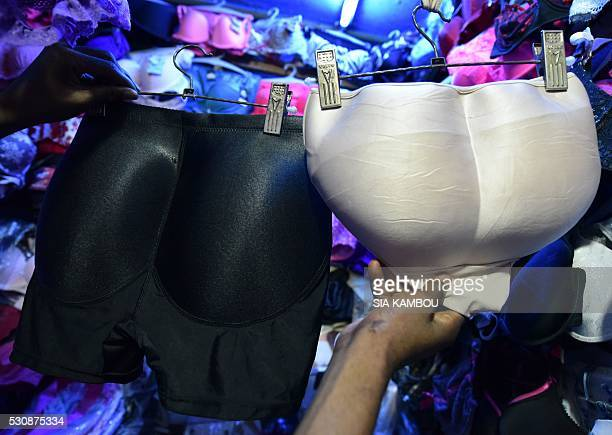 A seller shows padded panties in a market of Treichville suburb of Abidjan on July 23 2015 Some like creams others pop pills or splash out on padded...