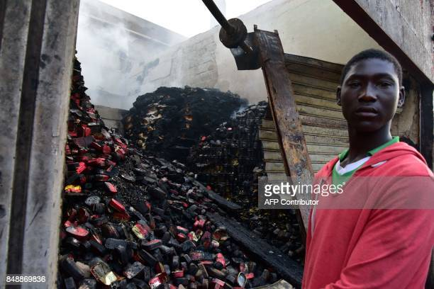A seller stands next to his shop in the market after a fire devastated the building during the night on September 18 2017 in Abobo neighborhood of...