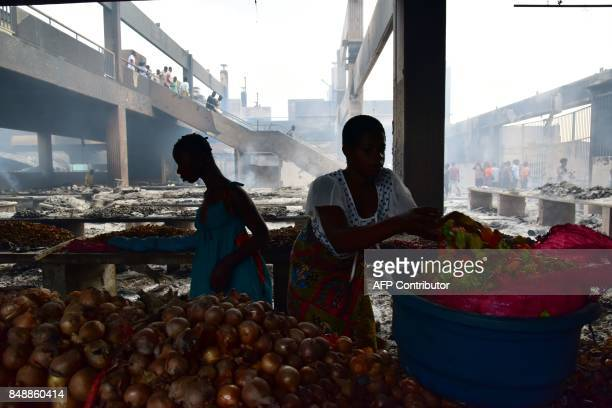 A Seller stands next to onions and peppers amid debris in the market after a fire devastated the building during the night on September 18 2017 in...