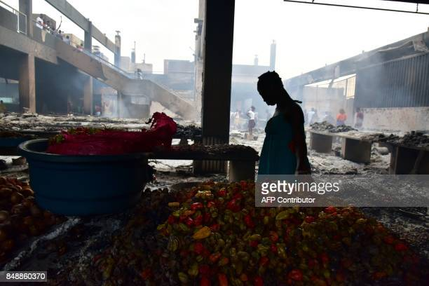 A Seller stands next to peppers amid debris in the market after a fire devastated the building during the night on September 18 2017 in Abobo...