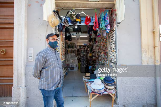 A seller stands outside his shop on May 23 2020 in Matera Italy Restaurants bars cafes hairdressers and other shops have reopened subject to social...
