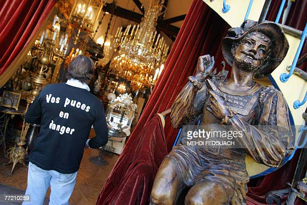 """Seller wears a tee-shirt reading """"Your flea market in danger"""" at a flea market in Saint-Ouen, Paris northern suburb, 06 October 2007. Traders at..."""