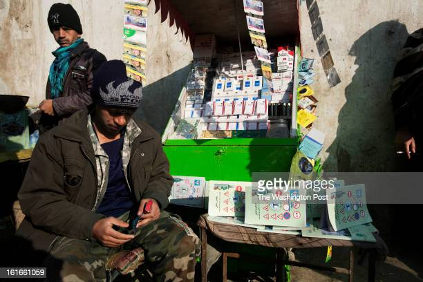KABUL AFGHANISTAN – JANUARY A seller works outside the traffic department in Kabul He provides cigarettes phone cards and booklets that explain the...