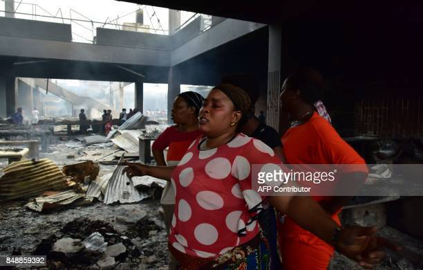 Sellers react amid debris in the market after a fire devastated the building during the night on September 18 2017 in Abobo neighborhood of Abidjan /...