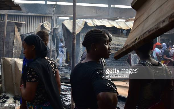 Sellers reacts amid debris in the market after a fire devastated the building during the night on September 18 2017 in Abobo neighborhood of Abidjan...
