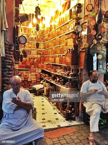 Sellers using mobile phone at their souk stall in Marrakech Morocco