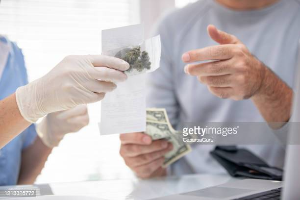 selling cannabis at cannabis store with receipt - cannabis store stock pictures, royalty-free photos & images