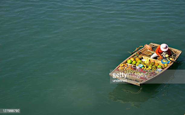 selling fruits in boat - floating market stock photos and pictures
