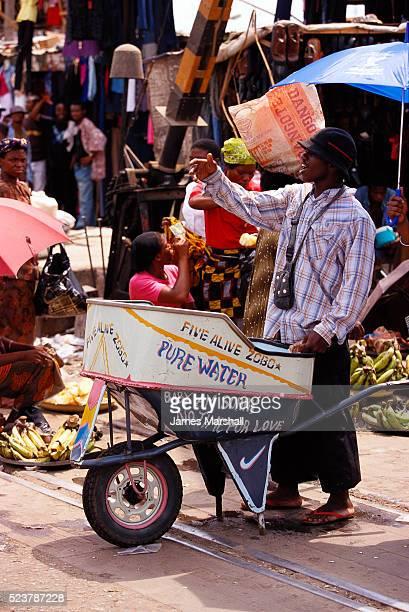 selling water in nigerian market - lagos stock-fotos und bilder