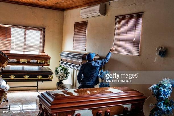 Sello Headbush, the owner of a Funeral Parlour adjusts Venetian blinds, inside the showroom where coffins are on display in Port Elizabeth on July...