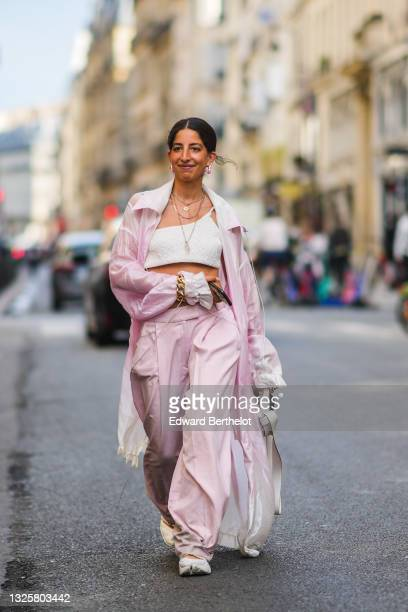 Selma Kaci Sebbagh wears earrings, a necklace, a pale pastel pink silky transparent trench coat, white bras / cropped top, golden chain wrist...
