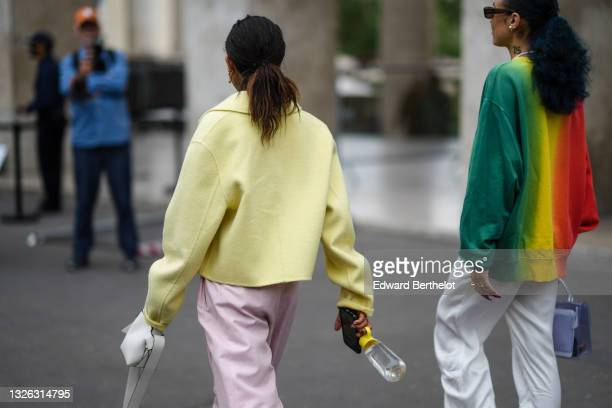 Selma Kaci Sebbagh wears gold and silver earrings, a pale yellow fluffy short jacket, pale purple large suit pants, a white leather handbag ; Hera...