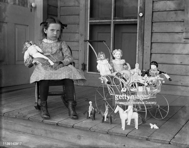 Selma Krueger sitting in a rocker on the porch holding a doll Watertown Wisconsin June 1900 Beside her is a buggy filled with dolls and other toys