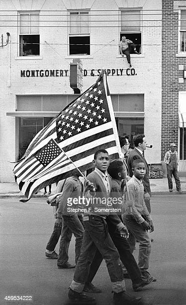 Selma to Montgomery civil rights marchers with Negro boys holding large and small American flags Man seated on windowsill in building in background...