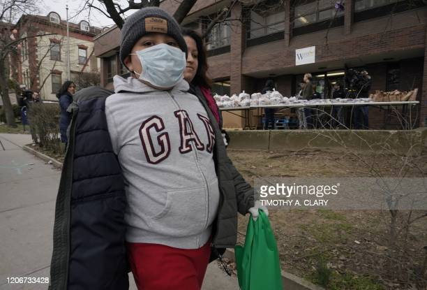 Selvin Jimenez age 10 wearing a protective mask carries some food away after National Guard troops gave supplies to residents of New Rochelle New...