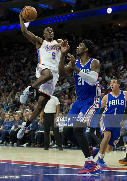 Semaj Christon of the Oklahoma City Thunder attempts a layup over Joel Embiid of the Philadelphia 76ers in the fourth quarter at Wells Fargo Center...