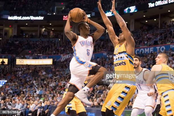 Semaj Christon of the Oklahoma City Thunder drives around Darrell Arthur of the Denver Nuggets during the first half of a NBA game at the Chesapeake...