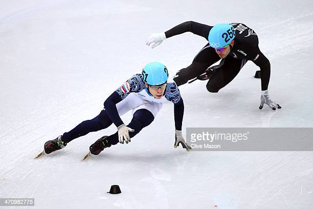 Semen Elistratov of Russia and Eduardo Alvarez of the United States compete in the Short Track Men's 5000m Relay Final A on day fourteen of the 2014...