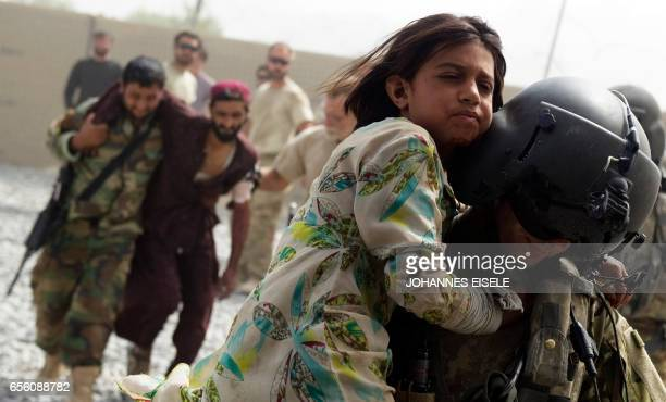 Semena a tenyear old wounded Afghan girl is carried by US army medic Stephan Flynn to a Medevac helicopter of 159th Brigade Task Force Thunder to be...