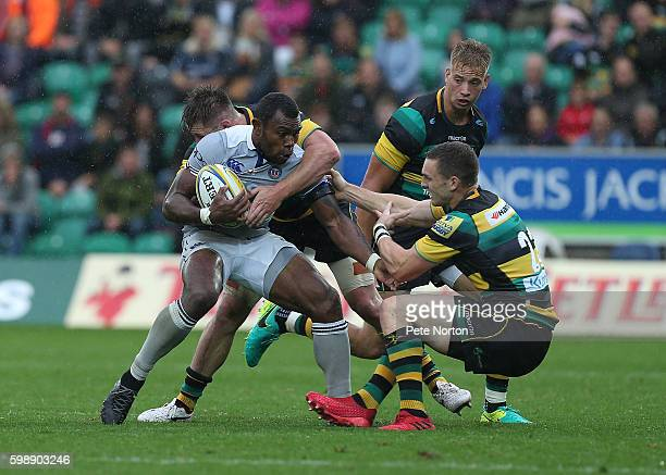 Semesa Rokoduguni of Bath is stopped by Teimana Harrison and George North of Northampotn Saints as Harry Mallinder looks on during the Aviva...