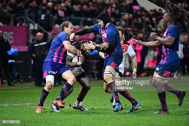 Semi Kunatani of Toulouse takes on Hugh Pyle of Stade Francais Paris and Meyer Bosman of Stade Francais Paris during the Top 14 match between Stade...