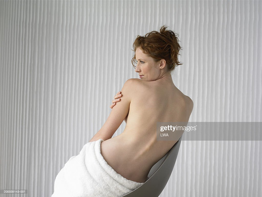 Semi nude woman on chair, rear view : Stock Photo