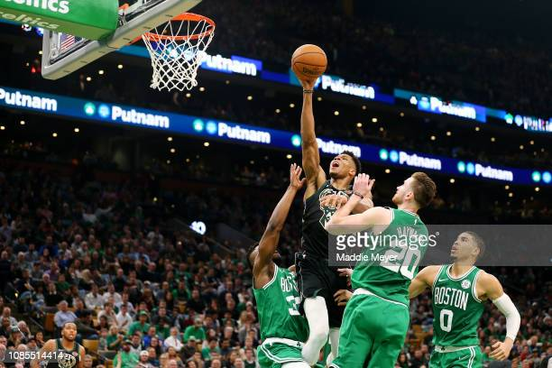 Semi Ojeleye of the Boston Celtics Jayson Tatum and Gordon Hayward defend a shot from Giannis Antetokounmpo of the Milwaukee Bucks at TD Garden on...