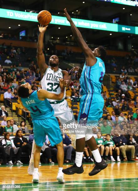 Semi Ojeleye of the Boston Celtics takes a shot over Marcus Paige of the Charlotte Hornets and Johnny O'Bryant III during the second half at TD...