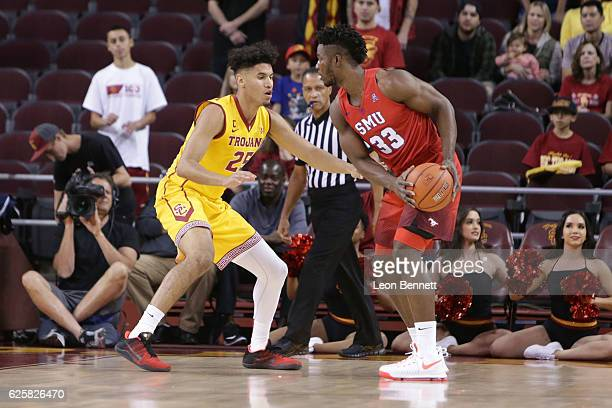 Semi Ojeleye of the SMU Mustangs handles the ball against Bennie Boatwright of the USC Trojans during a NCAA college basketball game at Galen Center...