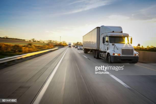 semi truck 18 wheeler and sunburst on highway - camión articulado fotografías e imágenes de stock