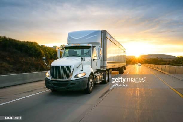 semi truck 18 wheeler on the highway at sunset - finanzwirtschaft und industrie stock-fotos und bilder