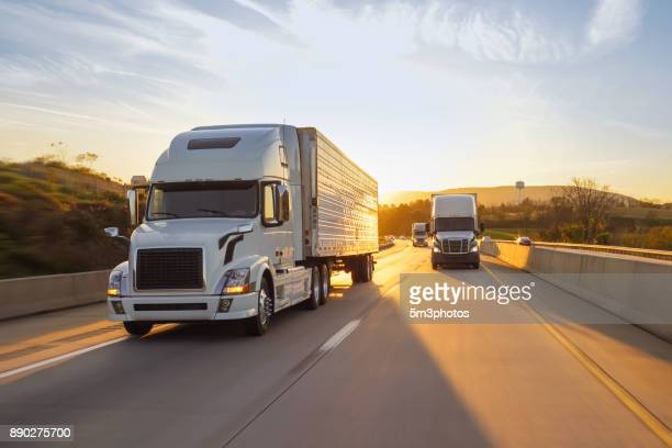 semi truck 18 wheeler sunrise on highway - vervoer stockfoto's en -beelden