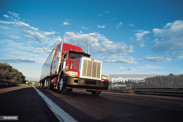 semi truck barreling down highway - trucking stock pictures, royalty-free photos & images