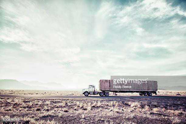 semi truck driving on deserted highway carrying hay - robb reece fotografías e imágenes de stock