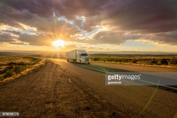 semi truck heading east bound with a beautiful sunset - trailer stock pictures, royalty-free photos & images
