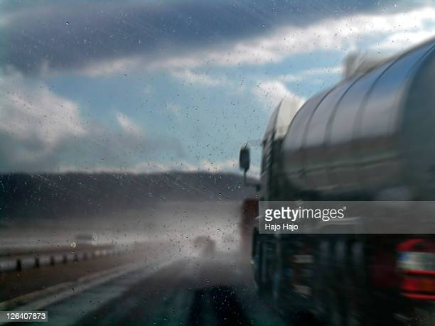semi truck of wet road - crash photos stock-fotos und bilder